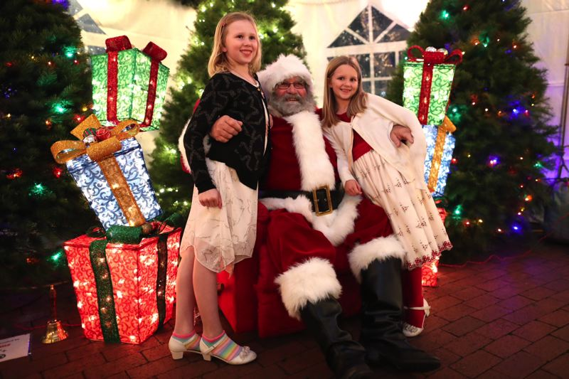 TIMES PHOTO: JAIME VALDEZ - Elizabeth Erland, 9, and Claire, 7, visit with Santa Claus at the Tualatin Commons on Friday.