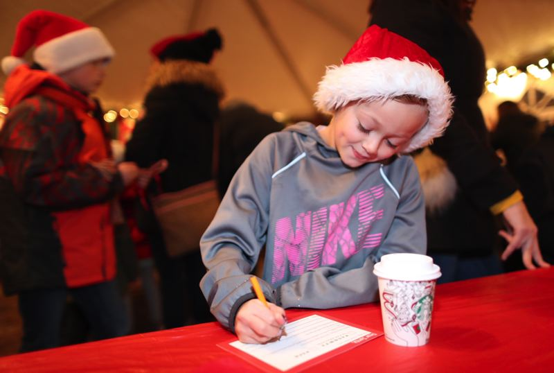 TIMES PHOTO: JAIME VALDEZ - Seven-year-old Erika Angel writes a letter to the troops at Starry Nights and Holiday Lights in Tualatin on Friday.