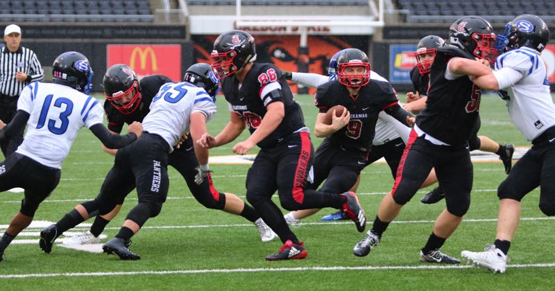 REVIEW/NEWS PHOTO: JIM BESEDA - Clackamas' James Millspaugh (9) follows lead blockers Chad Bletko (86) and Hudson Bishop (55) and scores on a 8-yard run in the third quarter of Saturday's OSAA Class 6A football championship game against South Medford at Reser Stadium in Corvallis.