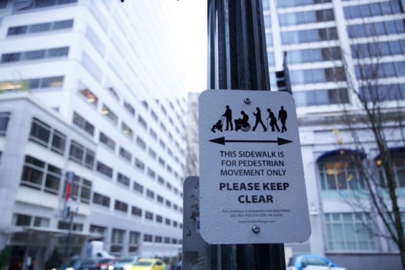 ERICKA CRUZ GUEVARRA/OPB - Signs prohibit people from blocking pedestrian traffic in front of the Columbia Sportswear flagship store in downtown Portland.