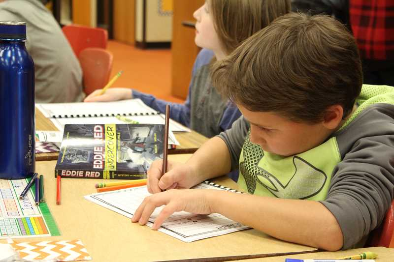 PIONEER PHOTO: KRISTEN WOHLERS - Colton Elementary student Zechariah Behrens works during Walk to Read on Nov. 29.