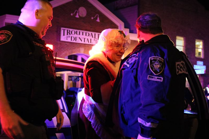 OUTLOOK PHOTO: ZANE SPARLING - Mrs. Santa Claus receives a warm welcome from Multnomah County Sheriff's deputies at Mayors Square in downtown Troutdale on Friday, Dec. 1.