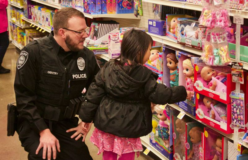 OUTLOOK PHOTO: CHRISTOPHER KEIZUR - Gresham Officer Brandon Gentry helps with the tough task of picking out a doll.