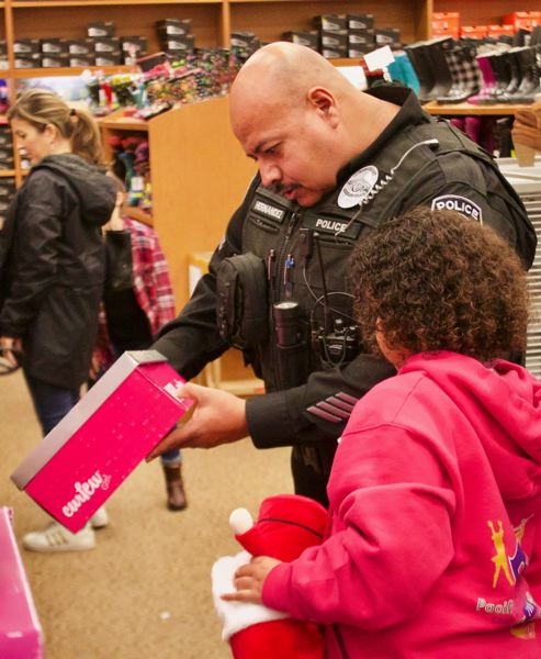 OUTLOOK PHOTO: CHRISTOPHER KEIZUR - Sgt. Manny Hernandez looks for the perfect pair of shoes. The kids not only bought toys, but also clothes and shoes to help brighten their holidays.