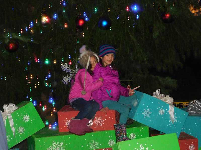 ESTACADA NEWS PHOTO: EMILY LINDSTRAND - Young friends are all smiles under the Christmas tree during Estacada's annual Lights on Broadway event.