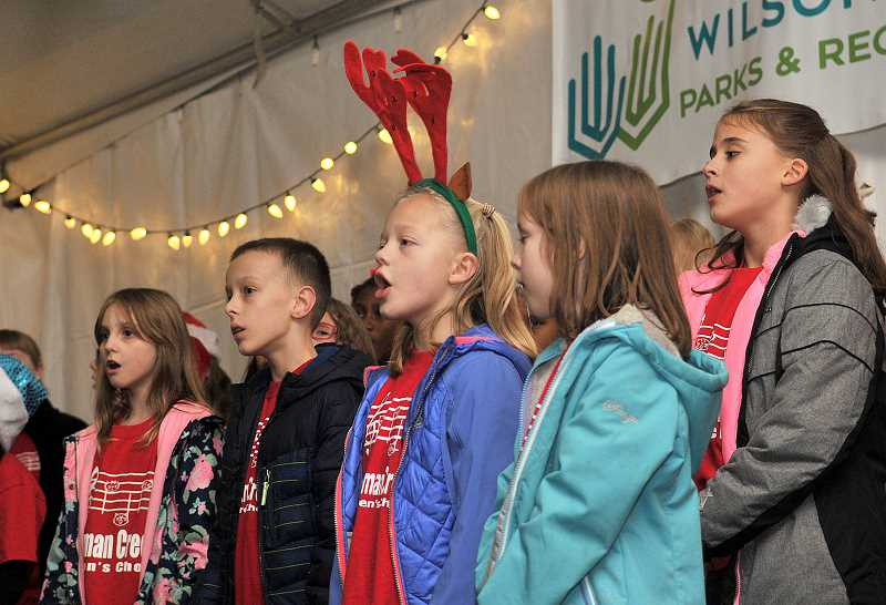 VERN UYETAKE - Members of the Boeckman Creek kids choir perform holiday song for the crowd gathered for the lighting of the tree.