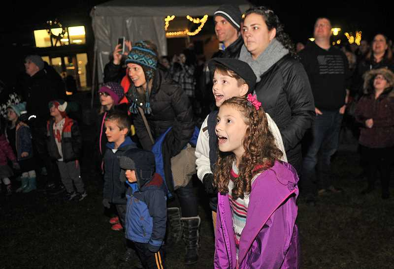 VERN UYETAKE - From left, Sophia, Alex and Angela Ferguson wait in anticipation of the lighting of the tree.