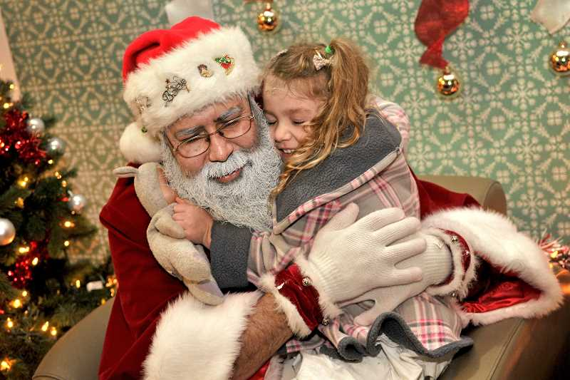 VERN UYETAKE - Callie Devault shares a special moment while visiting with Santa.