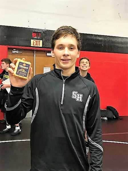 PHOTO CREDIT: AMY GADBOIS - St. Helens' Ethan Hubbs celebrates his 132-pound Tillamook Smoker Invitational championship with his cheese prize.