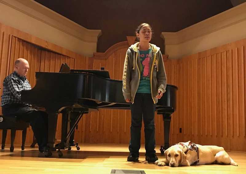 SUBMITTED PHOTO: YANA RAMOS - Yana Ramos rehearses onstage at Marylhurst University with her guide dog, Greta, resting at her side. Greta was in the audience Saturday when Ramos and the Marylhurst choir performed their holiday concert.