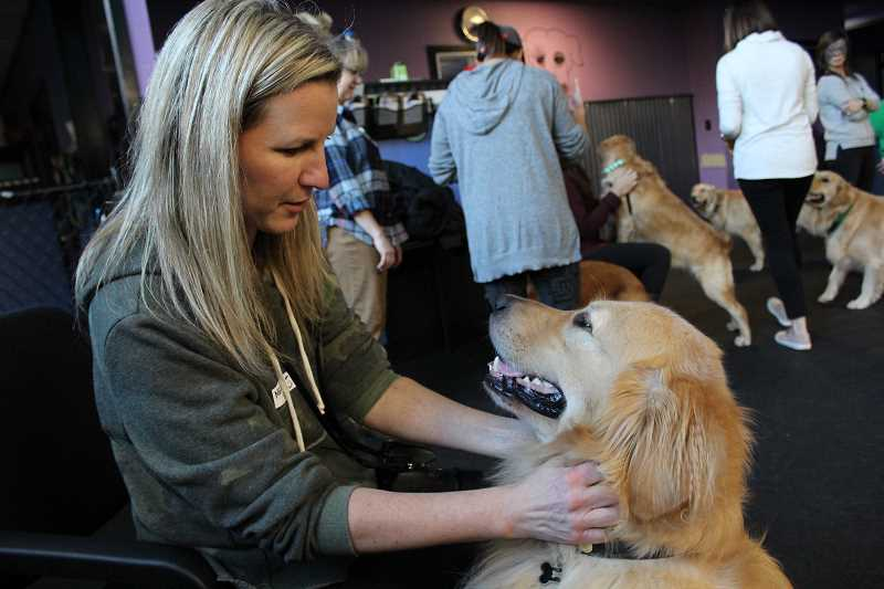 REVIEW PHOTO: SAM STITES - Melissa Heinonen takes a break from socializing with other dogs to give some love to her best friend Scout during the PDX Goldens meet-up Sunday at LexiDog in Lake Oswego.
