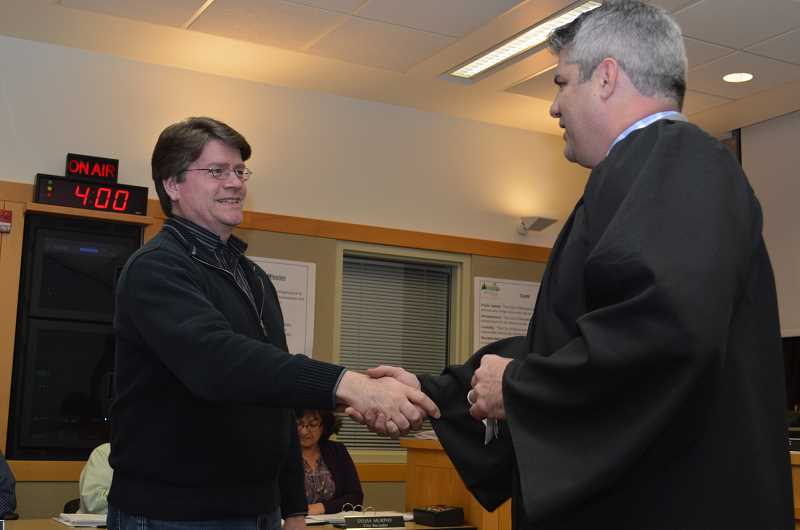 GAZETTE PHOTO: RAY PITZ - Sherwood Municipal Court Judge Brian Starns congratulates Russell Griffin after swearing him in a council member on Dec. 4.