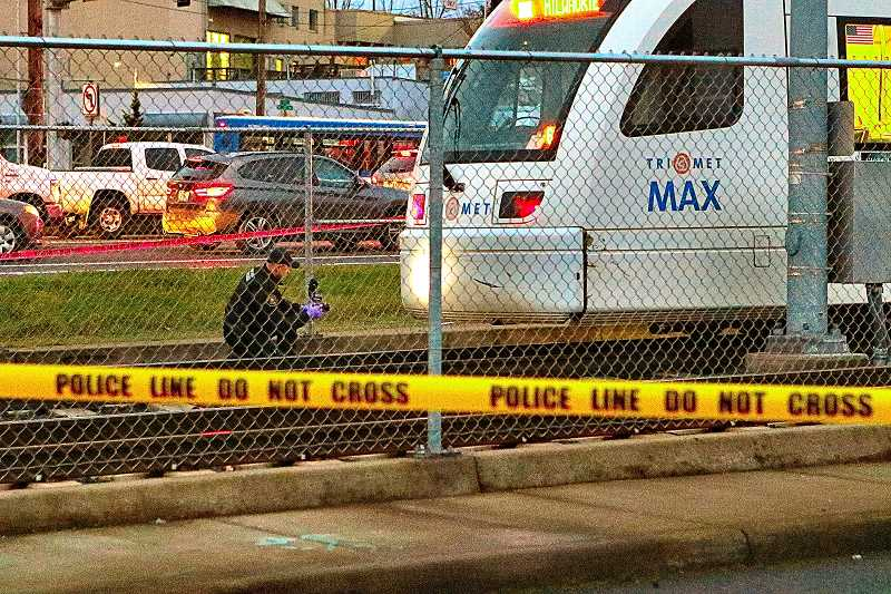 DAVID F. ASHTON - A police Forensics Division criminalist photographs the front of the MAX train that reported spotting a dead man at the tracks near the McLoughlin-S.E. 17th intersection, and then remained stopped there for hours during the investigation.