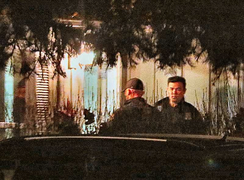 DAVID F. ASHTON - East Precinct officers, standing at a neighboring houses porch, keep careful watch on the suspects house while waiting for specially trained police arrive to try to defuse the situation.