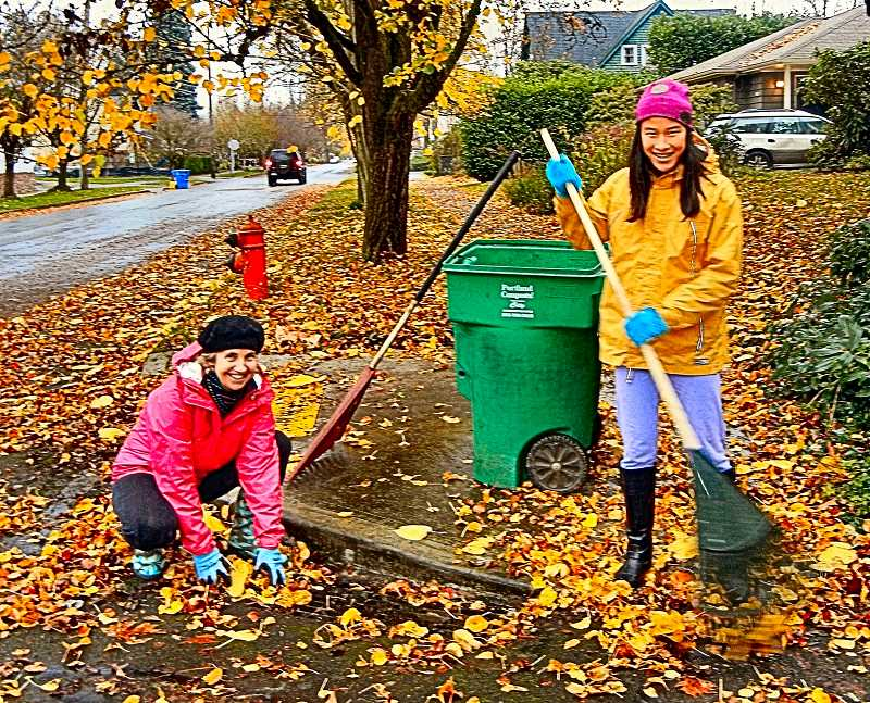ELIZABETH USSHER GROFF - In Woodstock, Mary Frazel and her daughter Ruby use rakes to keep the grated storm drain in front of their house free from leaves.