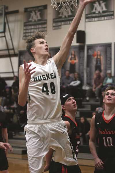 PHIL HAWKINS - North Marion senior Trevor Ensign lays the ball up in the Huskies' 68-62 win over Scappoose on Friday. Ensign is the lone player with size this season on a team that is able to throw a seemingly never-ending parade of athletic guards against opponents.