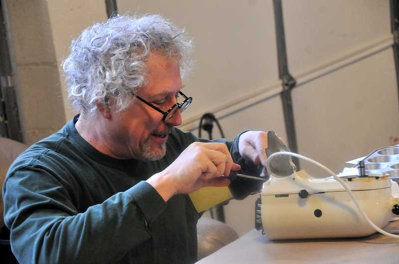 TIDNGS PHOTO: VERN UYETAKE - Kevin Bryck tries figure out what is causing a bad noise in a Kitchen Aid mixer.
