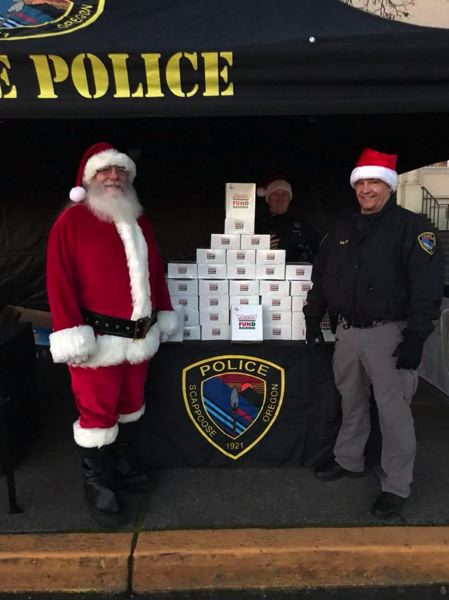 PHOTO COURTESY OF THE SCAPPOOSE POLICE DEPARTMENT - Santa Claus poses for a photo with Scappoose Police Chief Norm Miller during the Doughnut Day fundraiser on Saturday Dec. 9. The police department collected more than $3,000 and 550 pounds of donated food to benefit the food bank in Scappoose.