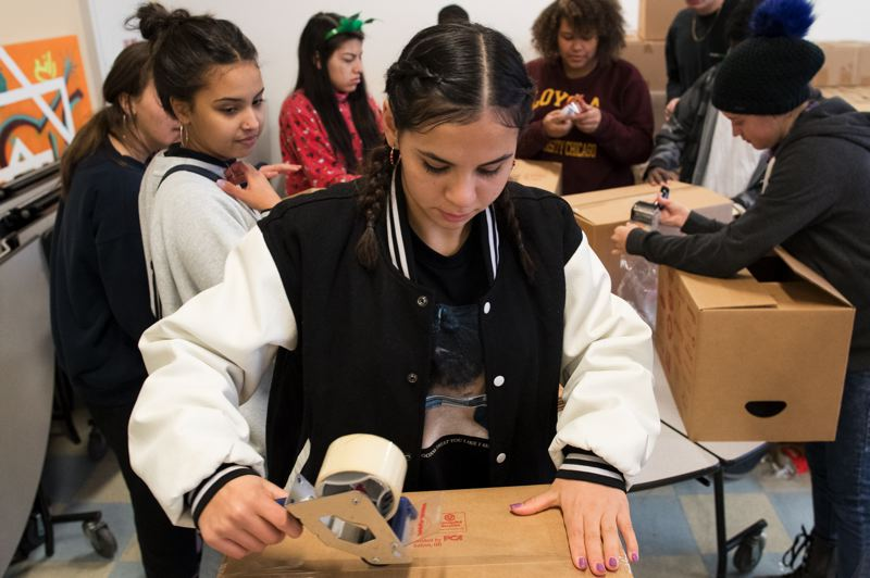 TRIBUNE PHOTO: JAIME VALDEZ - Laurie Yosemite-Caputi, a junior at Lincoln High School, tapes together a box as she and others prepare boxes of food for families in need during the school's annual food drive.