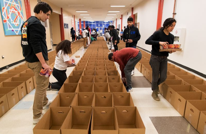 TRIBUNE PHOTO: JAIME VALDEZ - Students in the Black Student Union, Men of Color and Sisters of Color student groups at Lincoln High School carry flats of canned food and fill boxes with them for families in need Friday, Dec. 15.