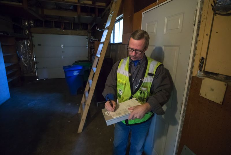 PAMPLIN MEDIA GROUP: JONATHAN HOUSE - Dave Scranton, senior electrical inspector for the City of Portland, makes notes during a house inspection.