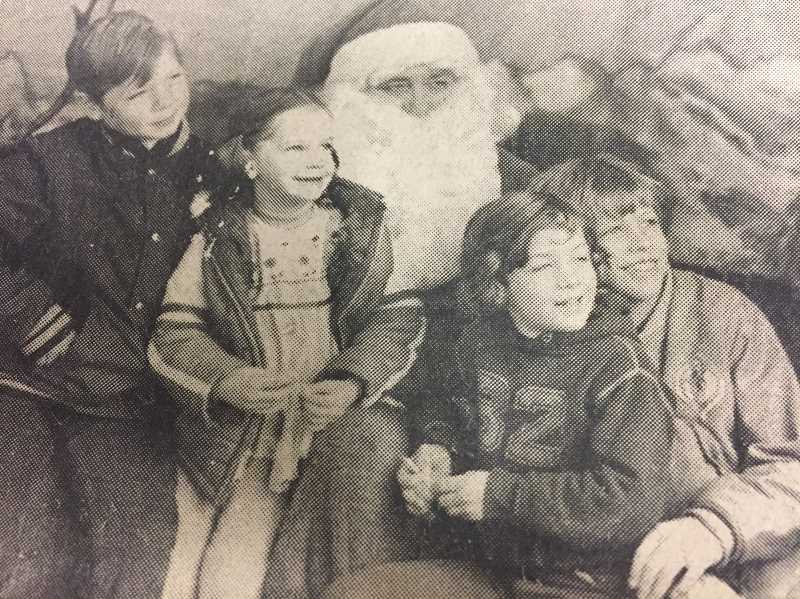 ARCHIVE PHOTO - In 1977, children visited with Santa after a holiday parade.