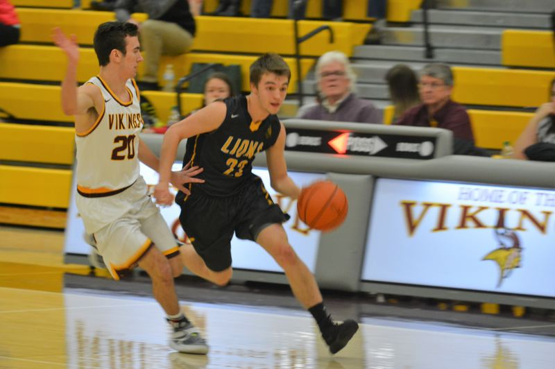 SPOTLIGHT PHOTO: JAKE MCNEAL - Lions senior guard Drake Dow (22) drives up the court against Forest Grove senior guard Kyle Thompson (20) Tuesday.