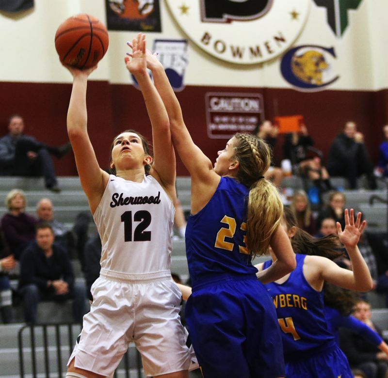 DAN BROOD - Sherwood junior post Kaytlin Cooke (left) takes a jump shot during the Lady Bowmen's game with Newberg on Friday. Sherwood outscored the Tigers, 46-38, but ended up having to forfeit the contest.