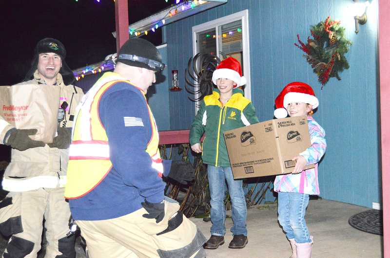 PIONEER PHOTO: CINDY FAMA - Colton Advanced EMT/Firefighter Casey Norlin and Lieutenant/Paramedic Alex Beaudoin are greeted with bags and boxes of food by Ray and Natalia Baurer on Dec. 21.