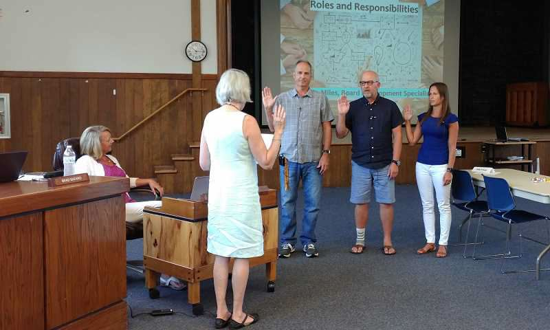 NEWS-TIMES FILE PHOTO: STEPHANIE HAUGEN - New Chairwoman Kate Grandusky swears in elected Forest Grove school board members (left to right) Brad Bafaro, Mark Everett and Valyrie Ingram in July.