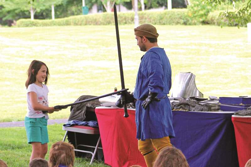 SPOKESMAN FILE PHOTO - Knights of Veritas member Michael Jones works with a volunteer to demonstrate proper sword technique during an educational swordfight Thursday, July 13 at Murase Park.