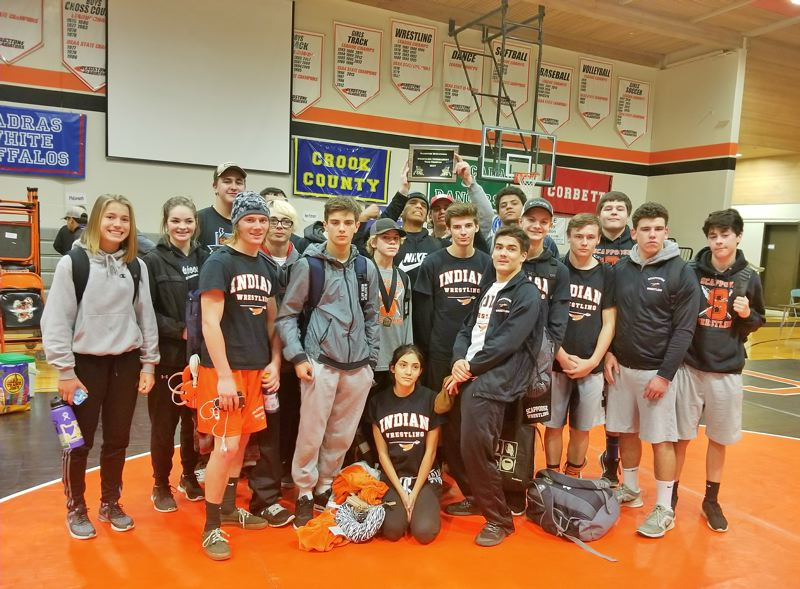 PHOTO COURTESY: NICK BYRD - Indians sophomore Emma Jones, far left, and the boys' team celebrate their respective Gladstone Tournament girls' 110-120-pound championship and boys' first-place tie with Class 5A Putnam.