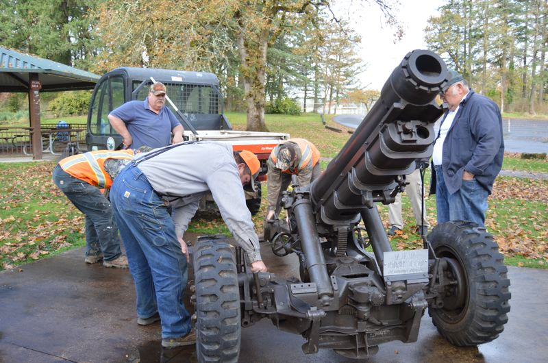 SPOTLIGHT FILE PHOTO - Members of St. Helens Veterans of Foreign Wars Post 1440 and St. Helens city staff work to reinstall a 105-mm Howitzer cannon in McCormick Park. The cannon was stolen last year and returned to the park this year after the theft case was settled.