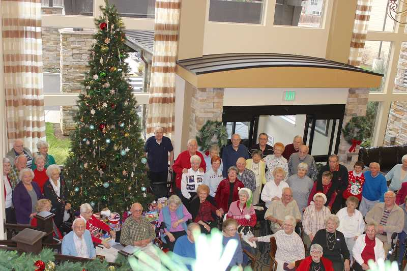 THE TIMES: MANDY FEDER-SAWYER - Residents from Bonaventure Senior Living gathered around the Christmas tree to celebrate the season of giving by donating gifts for foster youth.