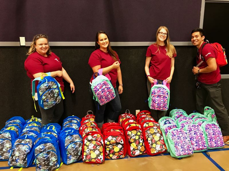 PHOTO COURTESY: CFCU - Modeling donated backpacks for Operation Backpack are Clackamas Federal Credit Union employees (from left) Hilary Kissell, Meagan Rice, Hannah Cole and Kevin Moran