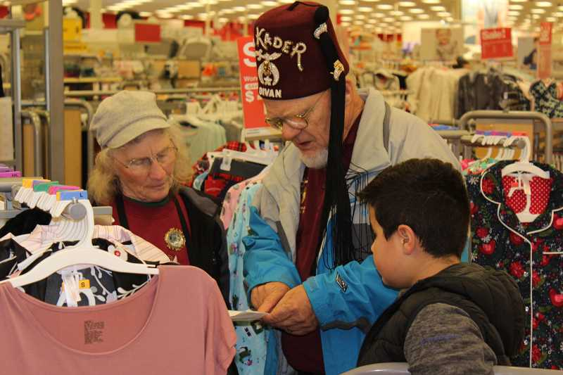 SPOKESMAN PHOTOS: COREY BUCHANAN - Al Kader Shriners members helped children pick out items for their parents at Target during the gift-giving event Tuesday, Dec. 19.