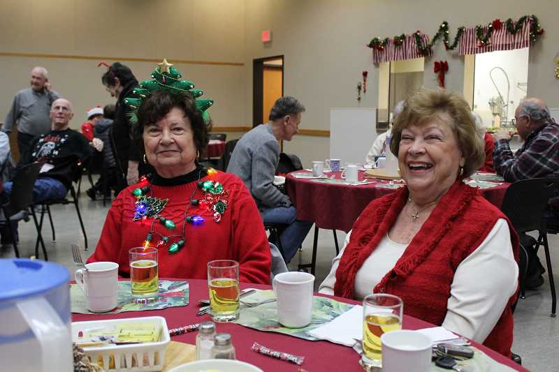 SPOKESMAN PHOTO: SAM STITES - Dolores Bennett (right) sports a red sweater complete with Christmas lights and a Christmas tree tiara at the Wilsonville Community Centers holiday luncheon Friday, Dec. 15.