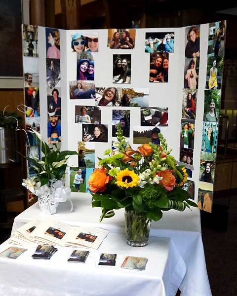 REVIEW PHOTO: CLAIRE HOLLEY - Photos of Deirdre Lynne Mackey and Grace Misztal cover a display inside Our Lady of the Lake Catholic Parish on Wednesday. Prayer cards featuring a painting by Tomasz Misztal, Grace's father, were also distributed to mourners.