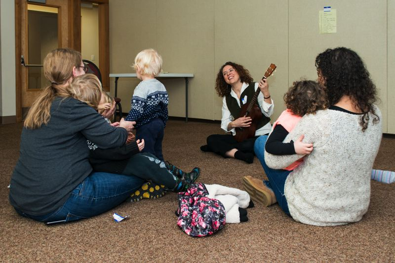 NEWS-TIMES PHOTO: CHRISTOPHER OERTELL - Lisa Peterson plays the ukulele and leads the group in a song toward the end of a preview class for a Music Together Generations series.