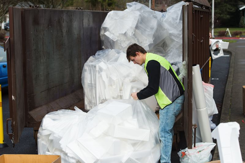 NEWS-TIMES PHOTO: CHRISTOPHER OERTELL - Huge bags of bulky Styrofoam blocks tower above Lance Sommer outside Lincoln Street Elementary School in Hillsboro during PlanetCon. He volunteered to collect the foam and load it into a recycling dumpster at the event.