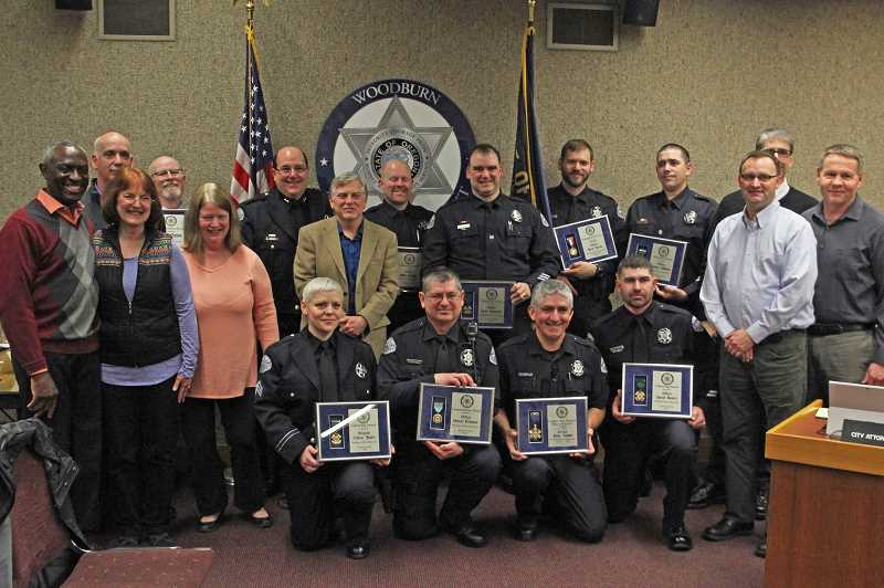INDEPENDENT PHOTO: JULIA COMNES. - The Woodburn Police Department honored 16 community members and police officers for 2016 and 2017 accomplishments. (From left) Ewart Brown, Paul Bickmore, Rhonda Judson, Tim Quinn, Mayor Kathy Figley, Police Chief Jim Ferraris, Sgt. Colleen Altabef, Eric Swenson, Officer Matt Stearns, Officer Robert Prinslow, Officer Geoff Carpenter, Officer Jorge Gaspar, Officer Aaron DeVoe, Officer Jarrod Bowers, Officer Zachary Williams, Shawn Baird of Woodburn Ambulance, City Administrator Scott Derickson, former Woodburn Fire District Chief Paul Iverson.
