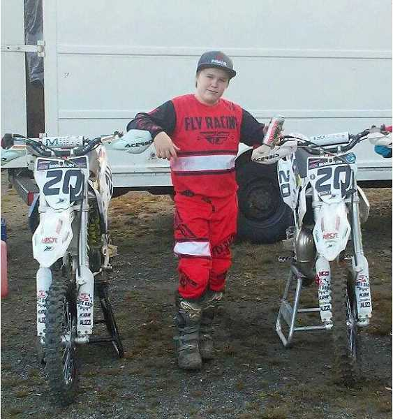 COURTESY PHOTO - Gales Creek's Rider Fisher poses with two of his motorcycles at one of his racing events last season.