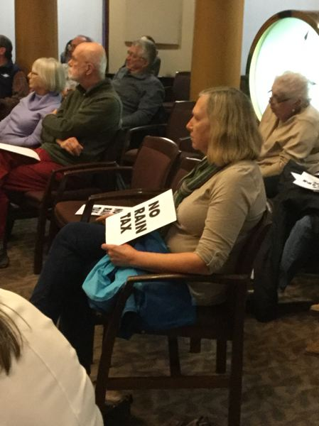 TRIBUNE PHOTO: STEVE LAW - Floating homeowners hold protest signs while attending Wednesday's public hearing.