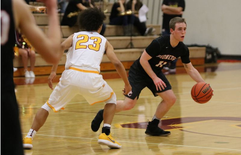 REVIEW/NEWS PHOTO: JIM BESEDA - Oregon City's Connor Curtis (11) looks for room to manuever around Central Catholic's Tyson Parker (23) during the first half of Friday's Mt. Hood Conference boys' basketball game.