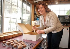 by: REVIEW, TIDINGS PHOTO: VERN UYETAKE - Lin Anderson works her cupcake magic in a small kitchen on Willamette Falls Drive. Her little cupcakes are delicious and beautiful.