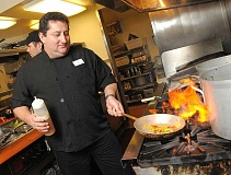 by: REVIEW PHOTO: VERN UYETAKE - Michael Schultz gets busy making lunch in the kitchen of The Stafford dining room. Schultz says it is just like cooking in his home.