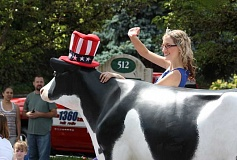 by: HILLSBORO TRIBUNE PHOTO: DOUG BURKHARDT - Betsy the cow and Megan Sprute, the Washington County Dairy Princess-Ambassador, were decked out in red, white and blue for this years Fourth of July parade in downtown Hillsboro.