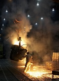 by: MICHAEL SHULTZ - An employee works with a ladle before pouring molten metal into a casting to create one of ESCO's products