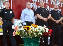 Photo Credit: TIDINGS PHOTO: VERN UYETAKE - Attendees at the Sept. 11 commemoration created a community bouquet that was to be placed in the new police station following the ceremony.