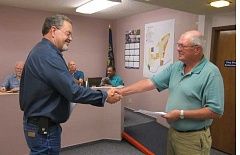 Photo Credit: BARBARA SHERMAN - READY TO TACKLE CITY BUSINESS - City Manager Dave Wells (left) congratulates Bob Olmstead after swearing him in as the newest King City city councilor at the Sept. 17 meeting.